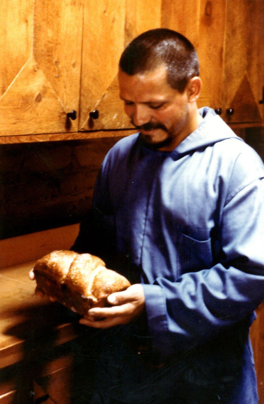 A young Abbot Philip admiring a loaf of bread he just baked (1976)