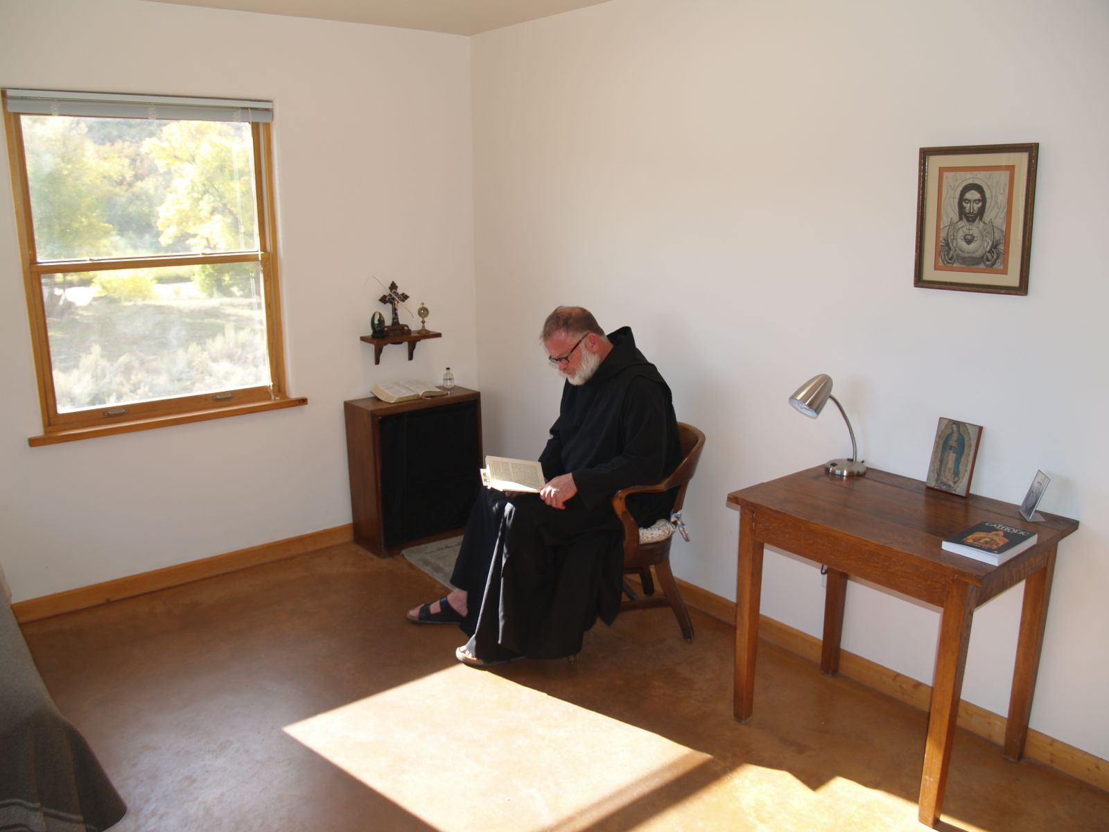 A brother doing Lectio Divina in his cell